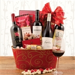 A red and gold oval metal basket with 4 bottles of wine and tons of Christmas treats.