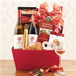 A red gift box with three bottles of Redtree California wine and tons of Christmas treats.