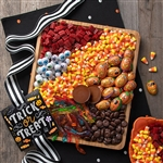 A wood serving platter filled with favorite Halloween candies, laid out like a charcuterie display.