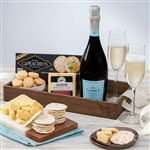 Gourmet cheese, crackers, chocolate, cookies and a bottle of La Marca Prosecco in a wooden crate.